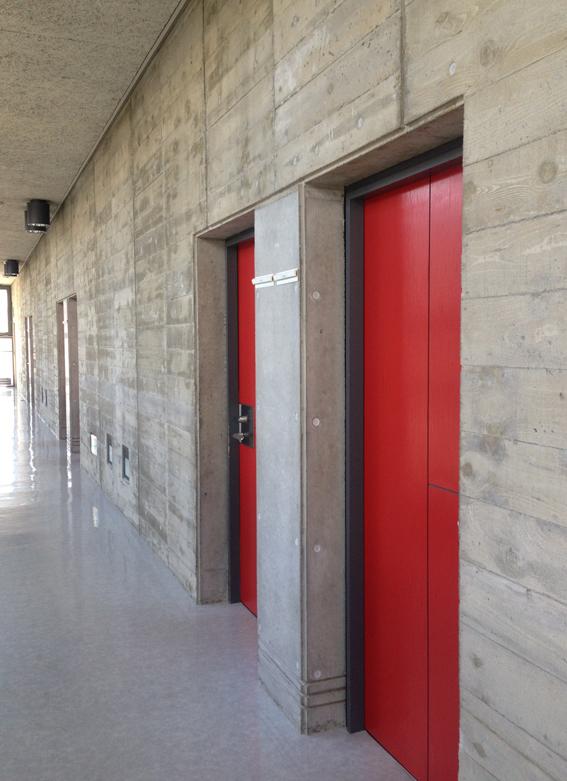 コンクリート打ちっ放しの壁に赤いドア